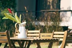 Положительный знак положил дальше деревянный стол с стулом в середине лужайки Украшенный с винтажными вазами цветка использование стоковые изображения rf