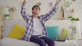 Положительный молодой азиатский человек в стеклах с ноутбуком сидя на кресле в живущей комнате получает выигрыш и банкноты задвиж сток-видео