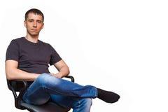 Положительный молодой кавказский человек, сидя на стуле кладя его fo Стоковое Фото