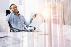 Положительный мужской работник офиса говоря на сотовом телефоне Стоковые Фото