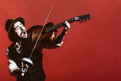 Положительный парень в студии имитирует скрипку стоковое фото