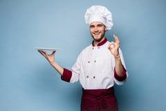 Положительный профессиональный счастливый шеф-повар человека показывая вкусный знак ок изолированный на свете - сини стоковое изображение