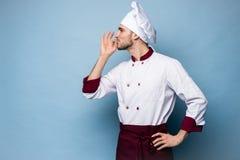 Положительный профессиональный счастливый шеф-повар человека показывая вкусный в порядке знак на свете - сини стоковые изображения