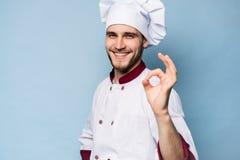 Положительный профессиональный счастливый шеф-повар человека показывая вкусный знак ок изолированный на свете - сини стоковые фото