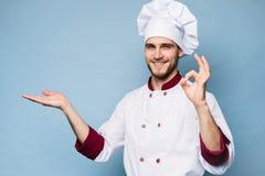 Положительный профессиональный счастливый шеф-повар человека показывая вкусный знак ок изолированный на свете - сини стоковая фотография rf