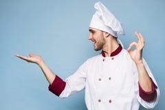 Положительный профессиональный счастливый шеф-повар человека показывая вкусный знак ок изолированный на свете - сини стоковое изображение rf