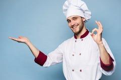 Положительный профессиональный счастливый шеф-повар человека показывая вкусный знак ок изолированный на свете - сини стоковая фотография