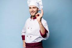 Положительный профессиональный счастливый шеф-повар человека показывая вкусный знак ок изолированный на свете - сини стоковое фото rf