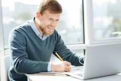 Положительный работник офиса делая примечания Стоковые Изображения