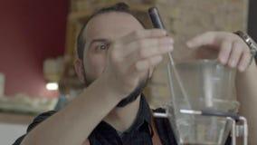 Положительный человек Barista подготавливает кофе переливать Stir, принимая температуру акции видеоматериалы
