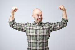 Положительный эмоциональный человек усмехается, показывается мышцы на его оружиях, чувствует гордым быть сильн стоковое фото rf