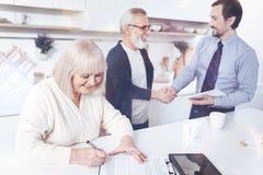 Положительным постаретый smilign договор страхования женщины подписывая стоковая фотография