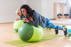 2 положительных женщины делая планку работают лежать на шарике баланса в спортзале Стоковое Изображение RF