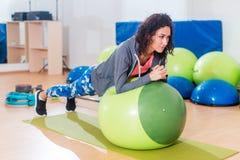 2 положительных женщины делая планку работают лежать на шарике баланса в спортзале Стоковые Фото