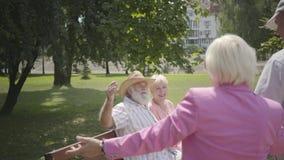 2 положительных зрелых пары встречают в парке Двойная дата старших пар Старики и женщины приветствуя один другого, человека видеоматериал