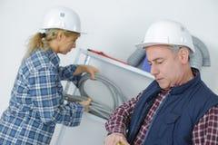 2 положительных работника в форме и шлемы на месте Стоковые Фото