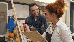 2 положительных студента отделения гуманитарных наук смеясь над в студии Стоковое фото RF