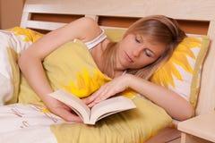 положите белокурое чтение в постель книги вверх по детенышам женщины взгляда стоковая фотография