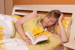 положите белокурое чтение в постель книги вверх по детенышам женщины взгляда стоковое фото rf