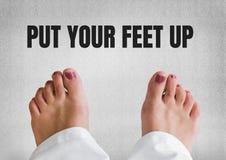 Положите ваши ноги вверх по тексту и босым ногам и серой каменной предпосылке Стоковые Фото