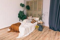 Положите в постель с одеялами и подушками в спальне нутряная комната стоковые фото