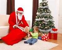 положите мальчика в мешки немного вне s santa принимая игрушки Стоковая Фотография RF