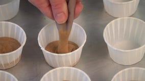 Положите тесто в бумажные стаканчики Тесто торта руки лить в поднос булочки акции видеоматериалы