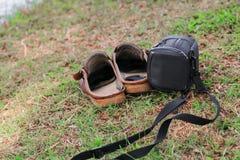 Положите черную и коричневую кожу в мешки ботинок старую на траве Стоковое Изображение