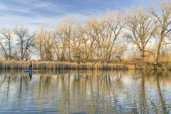 Полоскать стоит вверх paddleboard на спокойном озере Стоковое Изображение