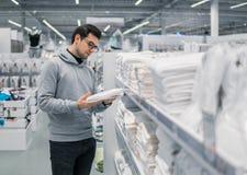 Полотенца мужского клиента проверяя и покупая в супермаркете Стоковые Фото