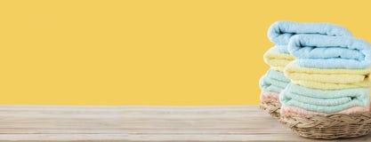 Полотенце на корзине на деревянной таблице с белым космосом стены и экземпляра на желтой предпосылке, можно использовать для прис стоковая фотография rf