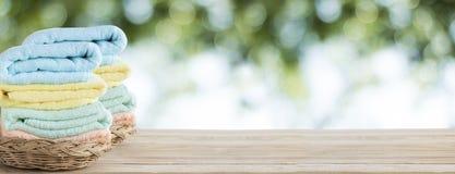полотенце на корзине на деревянной таблице с белым космосом стены и экземпляра на зеленом bokeh предпосылки природы, можно исполь стоковые фотографии rf