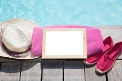 Полотенце соломенной шляпы и пустой шифер школы на террасе бассейна летом стоковые изображения rf