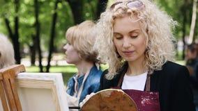 Полтава, Украина - может 2019: Группа в составе женщины различных возрастов учит нарисовать изображения в парке акции видеоматериалы
