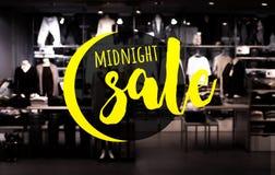 полуночный текст продажи с магазином одежды нерезкости в ноче Стоковая Фотография RF