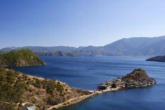 Полуостров Lige в открытом море озера Lugu и высоком небе стоковое изображение