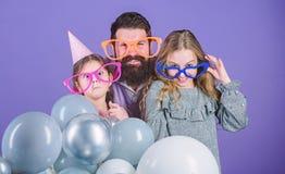 Получать смешной Семья отца и дочерей нося изумленные взгляды партии Дети отца и девушки наслаждаясь временем партии t стоковая фотография rf