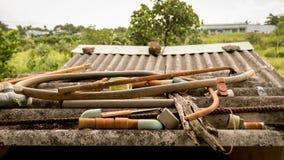 Получившиеся отказ трубы воды поливают из шланга пластиковые клапаны и ржавое старье металла на грязной рифленой крыше - саде сел стоковые фотографии rf