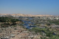 Получившиеся отказ хижины и дома морской водой с песочным путем от гор и немного деревьев стоковая фотография rf