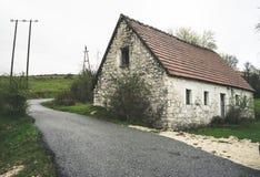 Получившийся отказ дом старого камня сельский Дом в деревне Покинутый преследовать каменный дом и грязная улица в древесинах Цвет стоковые изображения