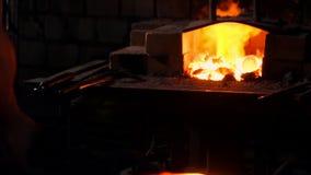 Получите, что горячий металл от печи сделать стрелку наклонить Дуновения молотка на горячем металле Искры летания металла во всех видеоматериал