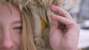Полу-портрет конца-вверх молодой кавказской девушки в клобуке меха мило наблюдая в камеру на предпосылке улицы зимы видеоматериал