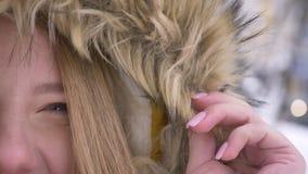 Полу-портрет конца-вверх спокойной молодой кавказской девушки в клобуке меха мило смеясь в камеру на улице зимы видеоматериал