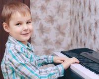 пользует ключом рояль Мальчик получает уроки рояля Руки мальчика на ключах рояля Стоковая Фотография RF