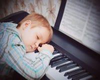 пользует ключом рояль Мальчик спит на ключах рояля Руки мальчика на ключах рояля Мальчик утомлен и уснувший после les рояля Стоковые Фотографии RF