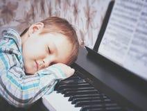 пользует ключом рояль Мальчик спит на ключах рояля Руки мальчика на ключах рояля Мальчик утомлен и уснувший после les рояля Стоковые Фото