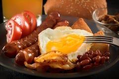 Польностью английский завтрак с взбитыми яйцами, беконом, сосиской, фасолями, томатами и соком вилка прокалывает яичный желток стоковая фотография rf