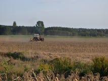 Польский фермер в тракторе работая в поле стоковое изображение