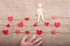 Полюбите концепцию с бумагами человеком и сердцами на linen потоках стоковые фото