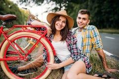 Полюбите пар при винтажные велосипеды сидя на обочине Стоковое Изображение RF